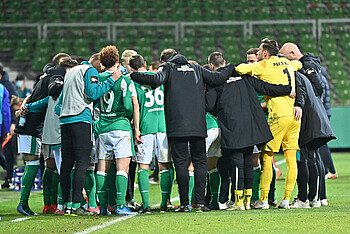 The Werder team huddle together before the start of extra time.