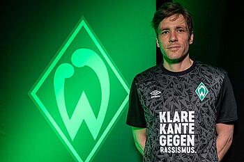 Clemens Fritz mit dem 'Klare Kante gegen Rassismus'-Shirt vor dem Werder Logo.