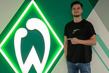 Tim van de Schepop vor der Raute des SV Werder Bremen nach seiner Vertragsunterzeichnung