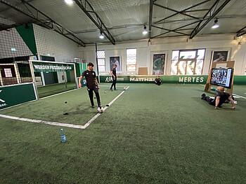 Zwei junge Mitarbeiter der Werder Fußballschule zeigen vor einem Bildschirm Übungen am Ball.