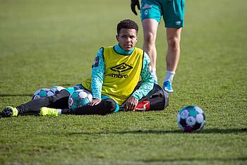 Felix Agu sitzt nach dem Werder-Training auf dem Boden.